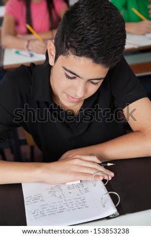 High angle view of teenage schoolboy reading paper in binder at classroom desk - stock photo