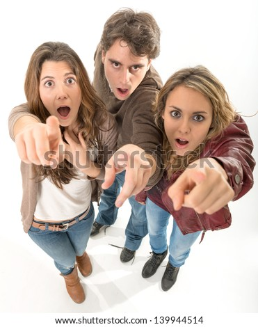 High angle view of three young friends pointing up with surprised expressions - stock photo