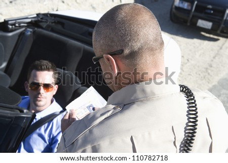 High angle view of traffic officer checking man's license - stock photo