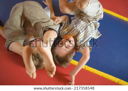 High angle view of two boys playing on an inflatable bouncy castle - stock photo