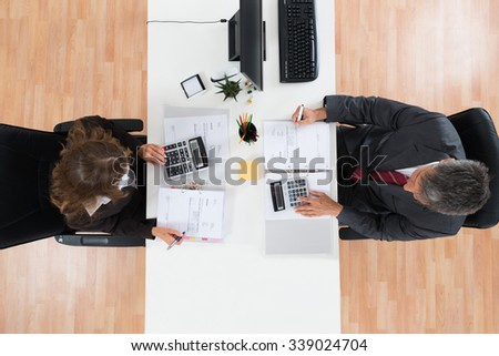 High Angle View Of Two Businesspeople Calculating Bills In Office - stock photo