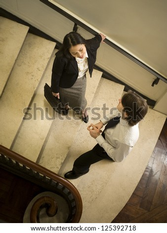 High angle view of two businesspeople chatting on stairway - stock photo