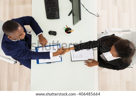 High Angle View Of Two Businesspeople Shaking Hand - stock photo