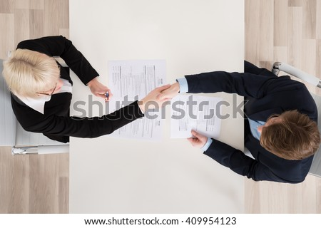 High Angle View Of Two Businesspeople Shaking Hand In Office