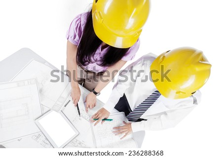 High angle view of two young architects discussing design project on the table, isolated on white - stock photo