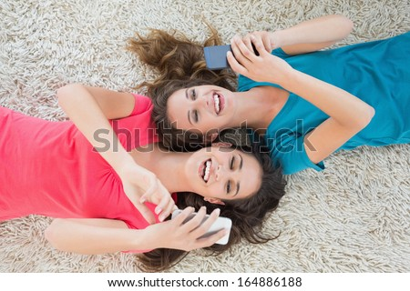 High angle view of two young female friends lying on rug and text messaging in the living room at home - stock photo