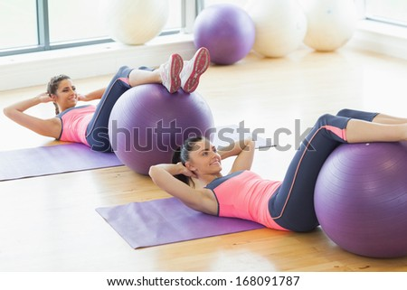 High angle view of two young women exercising with fitness balls at a bright gym