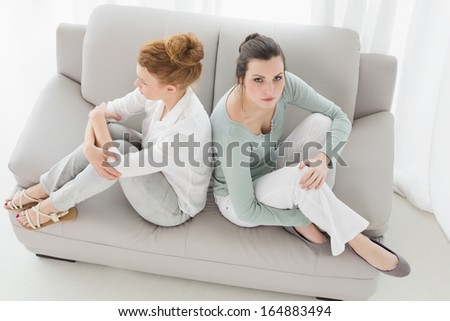 High angle view of unhappy young female friends not talking after argument at home on the couch