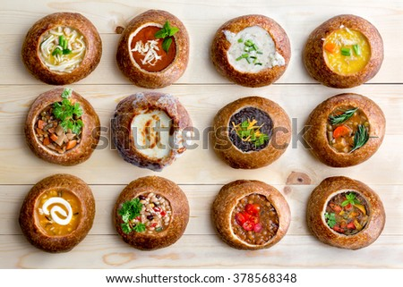 High Angle View of Various Comforting and Savory Gourmet Soups Served in Hollowed Out Bread Bowls on Wooden Table Surface - stock photo
