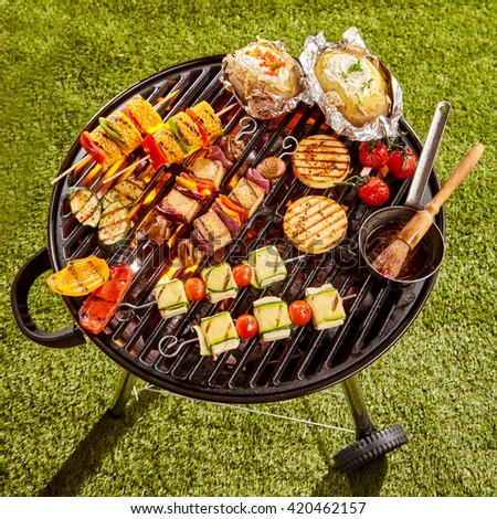 High Angle View of Various Vegetarian Kebabs and Vegetables Cooking on Grill with Basting Sauce in Sunny Yard on Summer Day