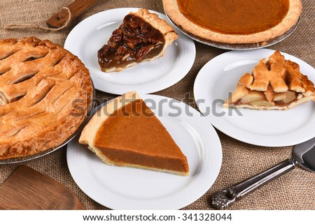 High angle view of whole pies and plates with slices. Traditional Thanksgiving desserts include, Pecan Pie, Apple Pie and Pumpkin Pie. - stock photo