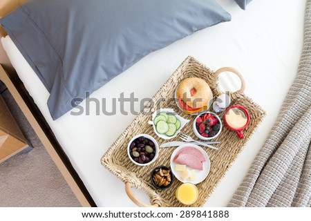 High Angle View of Wicker Breakfast Tray on Unmade Bed in Hotel Room - stock photo
