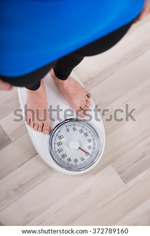 High Angle View Of Woman Measuring Body Weight On Weighing Scale
