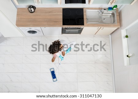 High Angle View Of Woman Mopping Floor In Kitchen