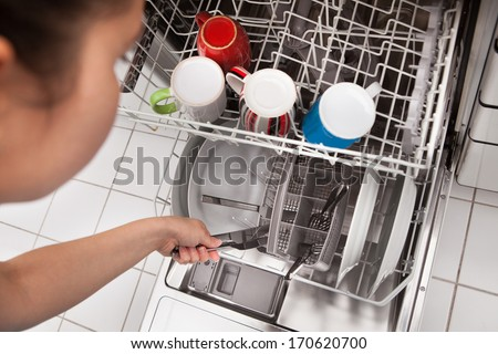 High Angle View Of Woman Placing Utensils In Dishwasher - stock photo