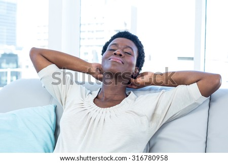 High angle view of woman relaxing with hands on neck on sofa at home - stock photo