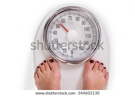 High angle view of woman's legs on weighing scale over white background - stock photo