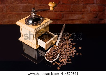 High Angle View of Wooden Spoon with Spilled Roasted Coffee Beans by Traditional Hand Grinder with Fresh Ground Coffee on Shiny Black Reflective Counter with Brick Wall in Background - stock photo