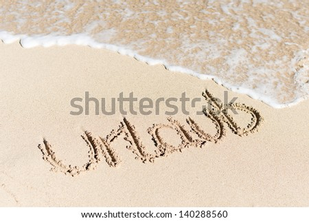 High angle view of word Urlaub written on sand by water surf - stock photo