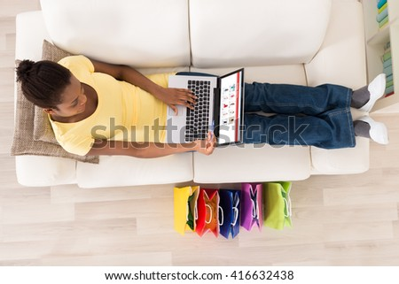 High Angle View Of Young African Woman Sitting On Sofa Shopping Online With Debit Card - stock photo