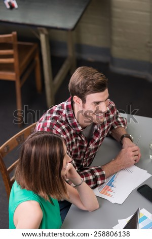 High angle view of young business people in a meeting seated around a table with paperwork and graphs in front of them