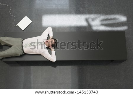 High angle view of young businessman yawning while lying on bench in office - stock photo