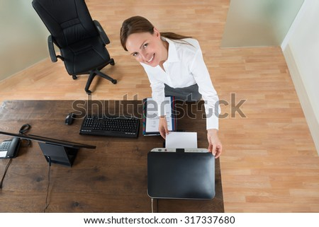 High Angle View Of Young Businesswoman Using Printer At Desk In Office - stock photo