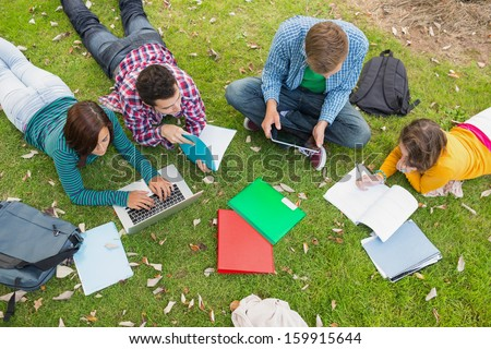 High angle view of young college students using laptop while doing homework in the park - stock photo