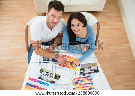 High Angle View Of Young Couple Choosing Color From Swatch - stock photo