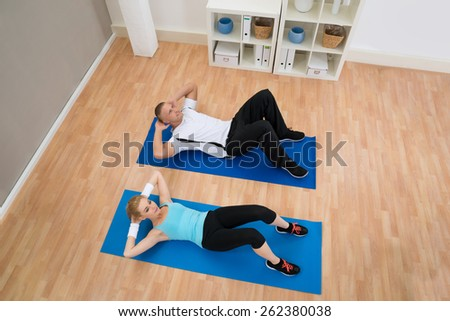 High Angle View Of Young Couple Doing Crunches On Exercising Mat - stock photo