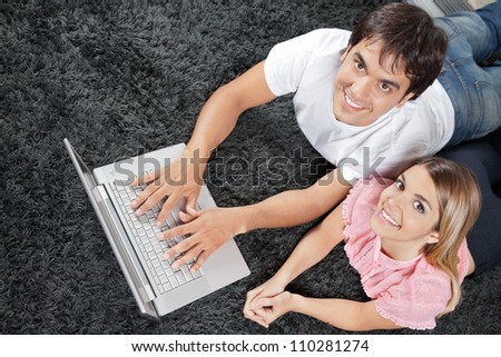 High angle view of young couple lying on rug with laptop