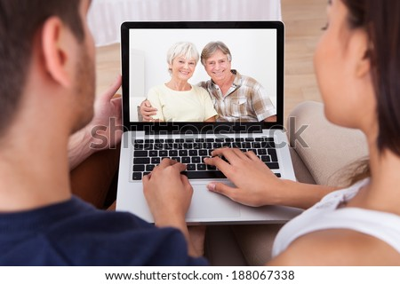 High angle view of young couple videocalling parents at home - stock photo