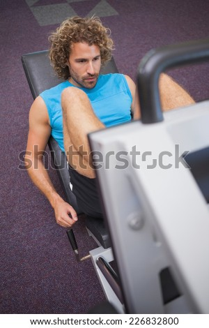 High angle view of young handsome man doing leg presses in the gym