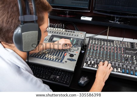 High angle view of young man mixing audio in recording studio - stock photo