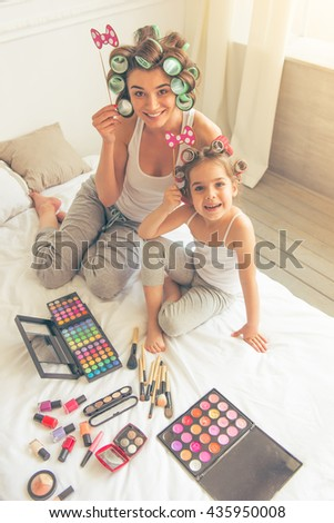High angle view of young mother and her daughter with hair curlers on heads holding paper bows on sticks, looking at camera and smiling, sitting on bed - stock photo