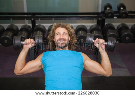 High angle view of young muscular man exercising with dumbbells in the gym
