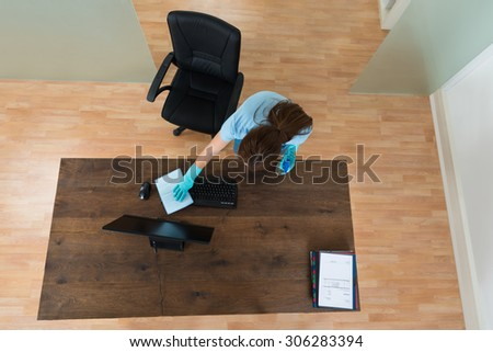 High Angle View Of Young Woman Cleaning Keyboard At Desk In Office - stock photo