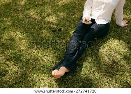 High angle view of young woman in jeans and white shirt resting in city park, sitting on grass and text messaging with mobile phone. Copy space, cropped view - stock photo