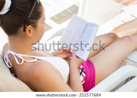High angle view of young woman in swimwear reading book on lounge chair at resort - stock photo