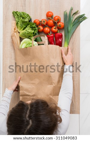 High Angle View Of Young Woman Removing Vegetables From Shopping Bag