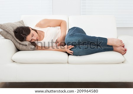 High angle view of young woman suffering from stomachache on sofa at home - stock photo