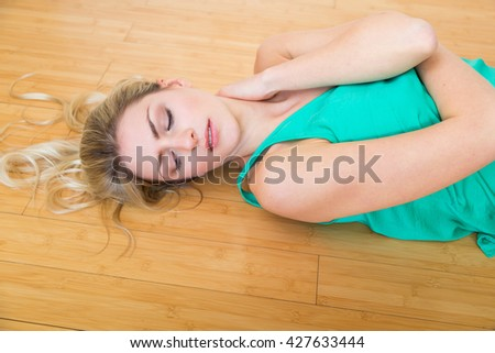 High angle view on cute serious blond young adult woman in green undershirt holding side of neck while laying down on hardwood floor