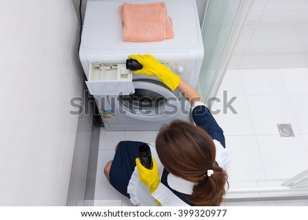High angle view on single female housekeeper preparing small front loading washing machine for a load of laundry