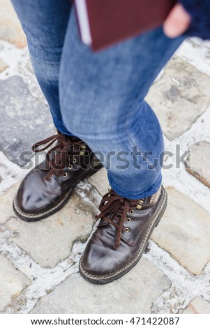 High angle view on woman's legs wearing brown shoes and blue jeans