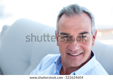 High angle view portrait of Happy man sitting on sofa st home