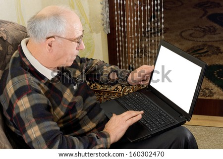 High angle view showing the blank screen of a balding senior man wearing glasses using a laptop computer to surf the web - stock photo