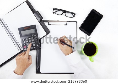 High angle view table of hands working with calculator and paperwork - stock photo