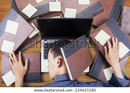 High angle view table of male student napping on laptop with textbooks and post-it - stock photo