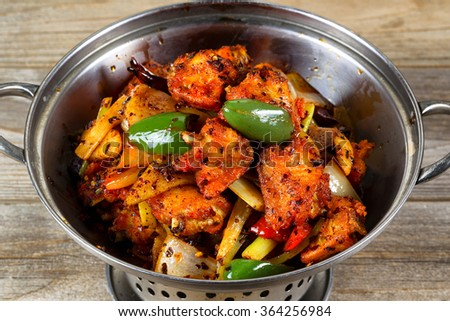 High angled view of a stainless steel cooking pot filled fried chicken and vegetables on rustic wood.   - stock photo