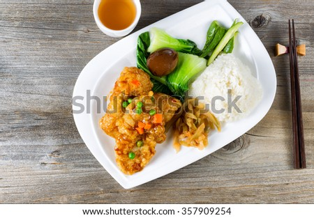 High angled view of lunch consisting of fried bread coated fish, bok choy, rice, egg, and on white plate. Chopsticks and green tea in background.  - stock photo